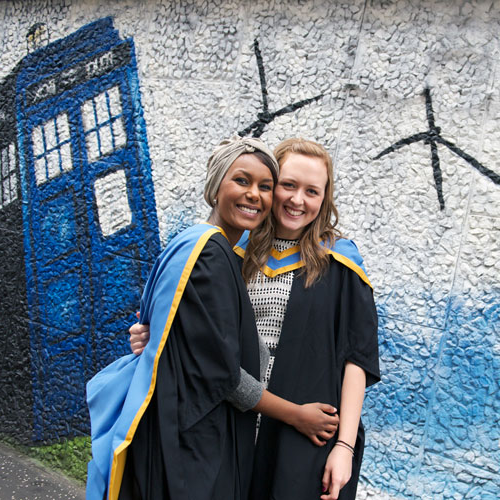 two female students smiling and hugging after graduating