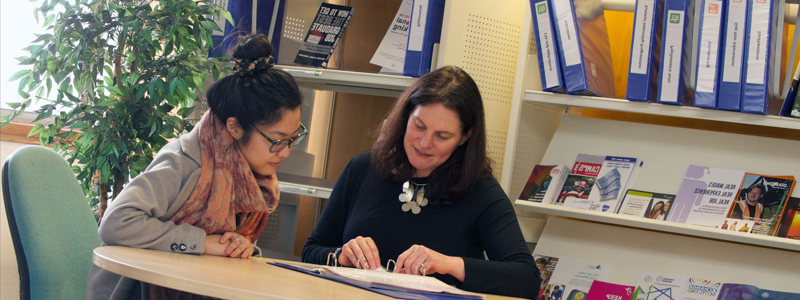 a careers adviser sits with a student looking at documents on the desk