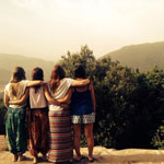 four students with arms round each other look out over the view of a country