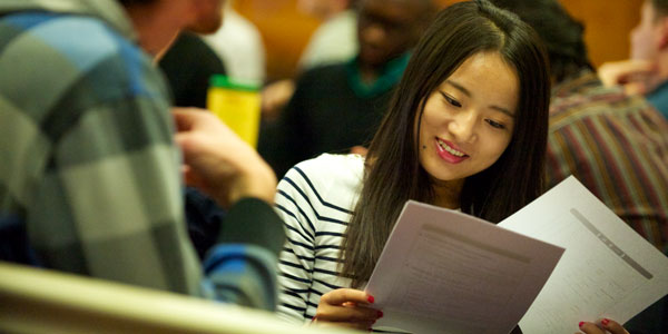 a female student looks at A4 pages in her hands with a smile on her face